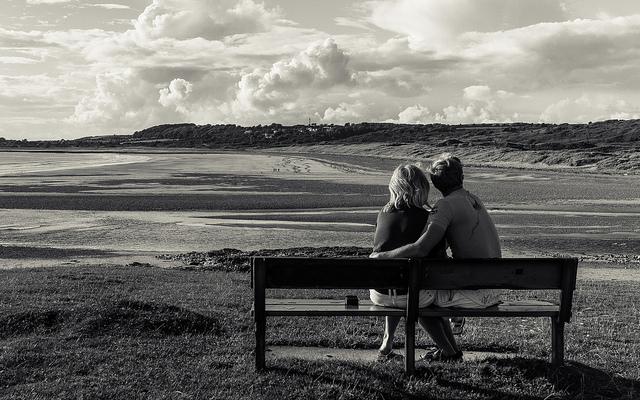 Couple assis sur un banc devant le bord de mer.